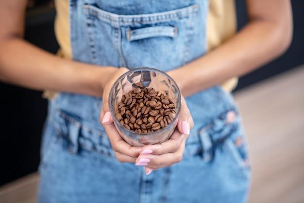全粒豆コーヒー。美しいコーヒー豆のガラスを保持しているマニキュアを持つ女性の優雅な手、顔なし