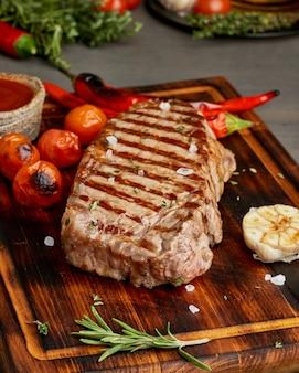 全牛肉ステーキ、木製のまな板に揚げたサーロイン。ケトケトン食。クローズアップ、側面図