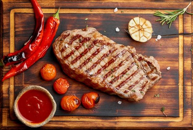Whole beef steak, fried striploin on wooden cutting board. keto ketogenic diet.