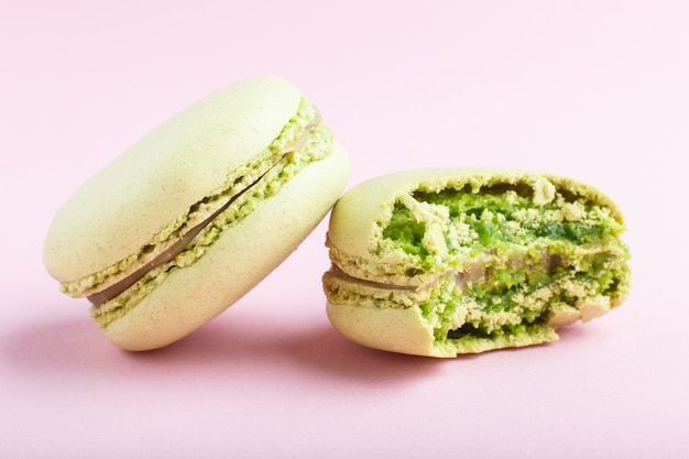 Whole and bitten green macarons or macaroons cakes on pastel pink background