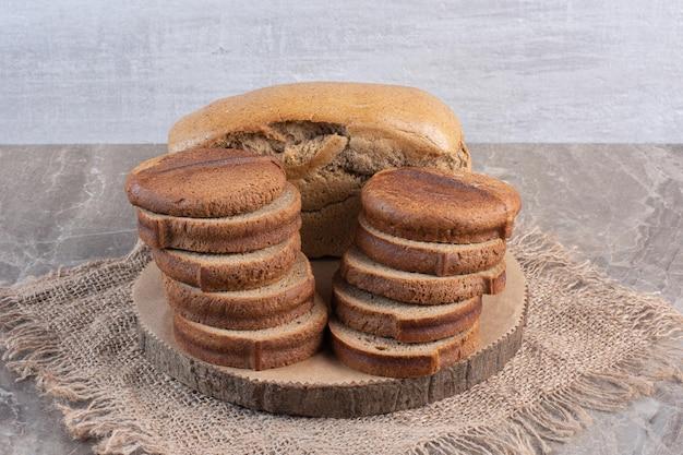 Whole bread block behind stacks of sliced brown bread on a board on marble background. high quality photo