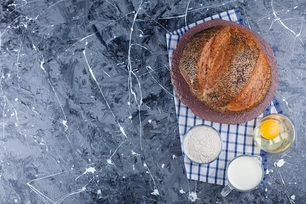 Цельный хлеб, яйцо, мука и молоко на кухонном полотенце на синем фоне.