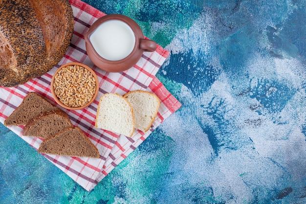 青の背景に、ティータオルに全粒粉パン、穀物、ミルク。