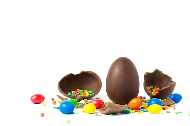 Whole and broken chocolate easter egg and multi colored sweets . concept of celebrating easter. copy space.