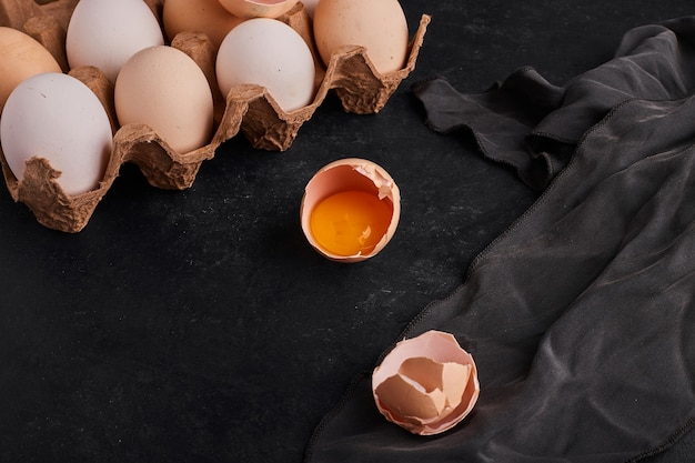 Whole and broken eggs on the black table.