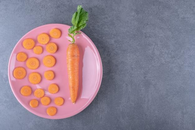 Целая морковь с нарезанной морковью на тарелке, на мраморной поверхности.