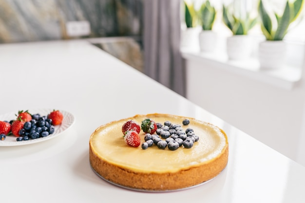 Whole cheesecake with fresh berries on a white table in modern kitchen.