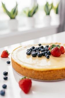 新鮮なイチゴとブルーベリーが白いモダンなキッチンの白いテーブルに全体のチーズケーキ。