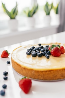 Whole cheesecake with fresh strawberries and blueberries on a white table in white modern kitchen.