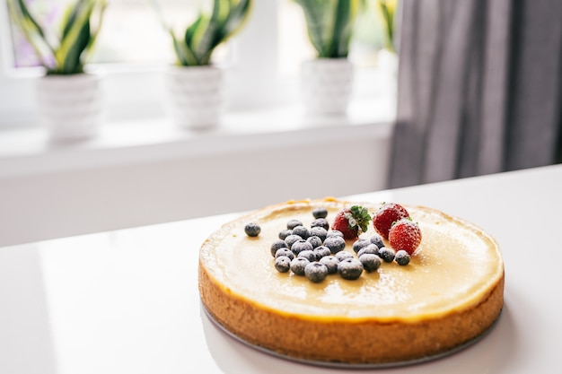 Whole cheesecake with fresh strawberries and blueberries on a white table in white modern kitchen