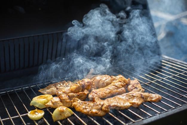 사랑스러운 고기 연기와 함께 뜨거운 바베큐 숯불 바베큐 그릴에 구운 전체 치킨, 구이의 개념