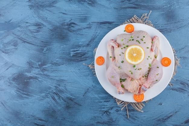 Целая курица, лимон и нарезанная морковь на тарелке на мешковине, на синем фоне.