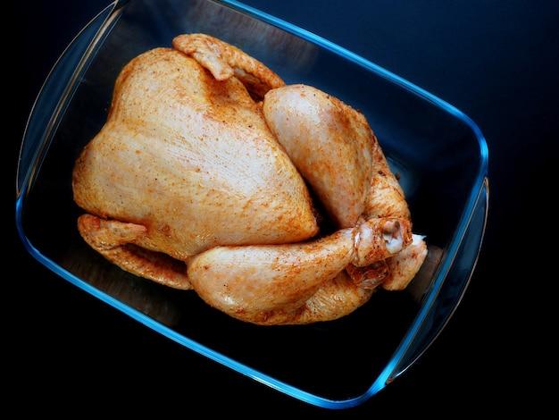 暗い背景のガラス製のベーキング皿で焼くために準備された丸ごとの鶏肉