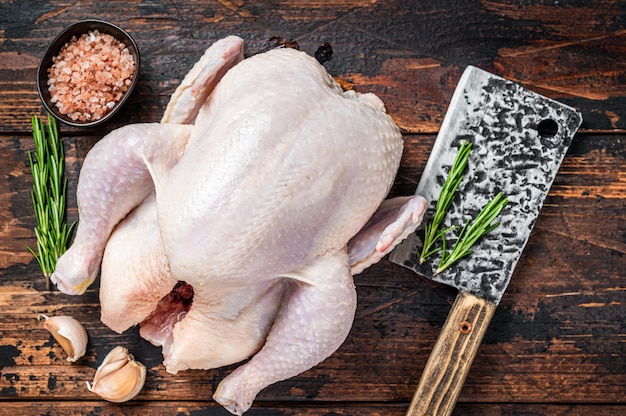鶏肉全体、肉切り包丁を備えた精肉店のテーブルに生の鶏肉。暗い木の背景。上面図。