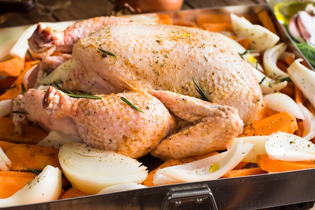 Whole chicken seasoned uncooked with chopped vegetables carrots potatoes onions, rosemary