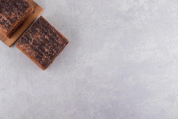 전체 초콜릿 케이크는 나무 커팅 보드에 배치됩니다.
