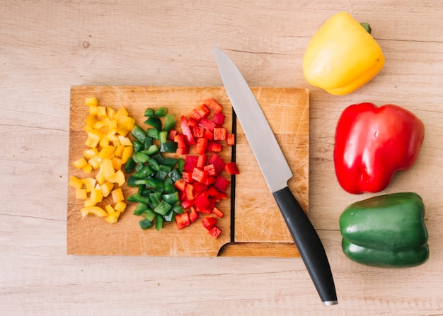 Whole and chopped red; green; yellow bell peppers on chopping board with sharp knife against wooden backdrop