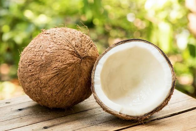 自然の表面にココナッツ全体とココナッツの半分。