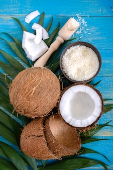Whole coconut nut, shell, coconut flakes, green palm leaves on a blue wooden background. top view, flat lay. tropical theme.