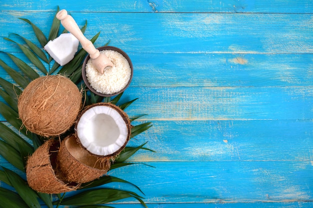 Whole coconut, shell, green palm leaves on a blue wooden background. copy space. top view, flat lay. tropical background.