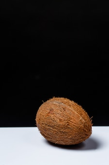 Whole coconut on a table on a black