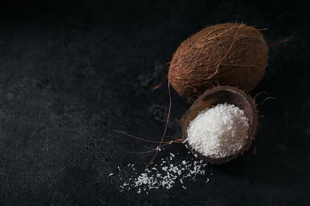 Целый кокос с кокосовой стружкой на черном фоне