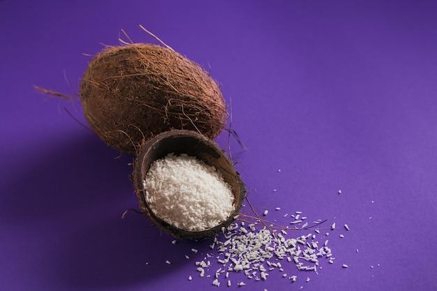 Целый кокос с кокосовой стружкой на фиолетовом фоне