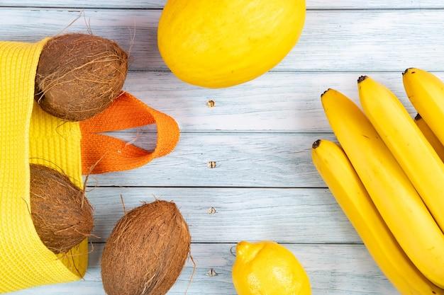 黄色いバッグにココナッツ全体、青い木製の背景にバナナとメロン。