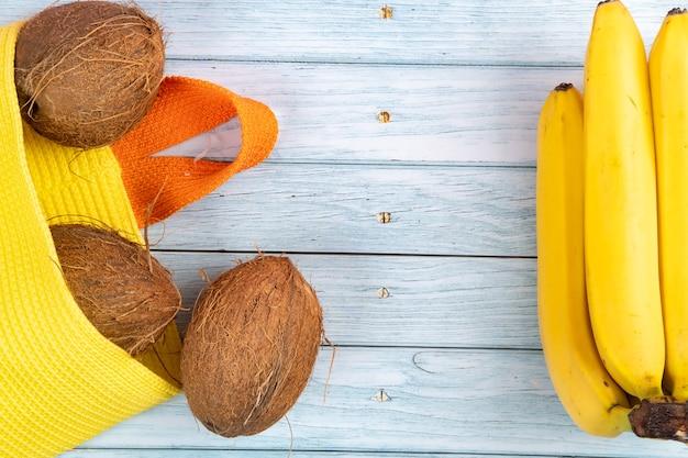 黄色いバッグに横たわっているココナッツ全体と青い木製の背景にバナナ。