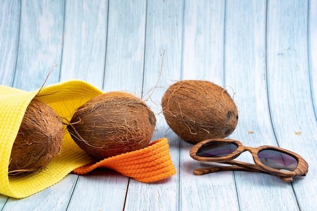 青い木製の背景に黄色のバッグとグラスに横たわっているココナッツ全体。