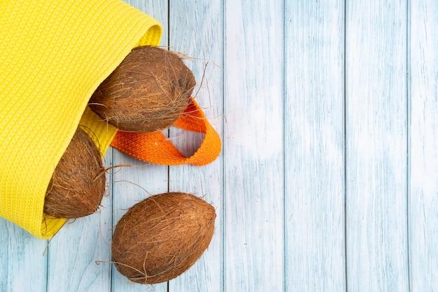 青い木製の背景に黄色のバッグに横たわっているココナッツ全体