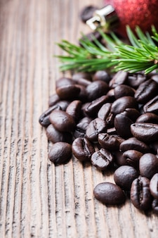 Whole coffee bean with fir tree branch and red ball on old wooden surface