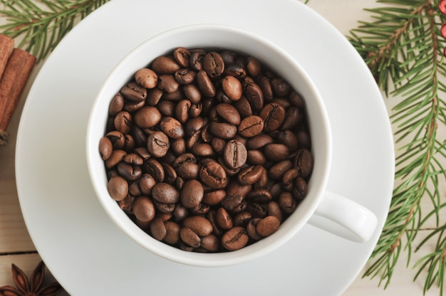 Whole coffee beans are poured into a coffee cup