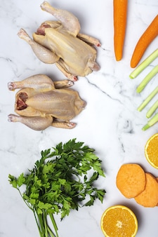 Whole coquelet chickens with raw vegetables ready to cook