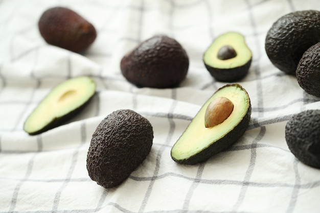 Whole and cut avocados on dishcloth