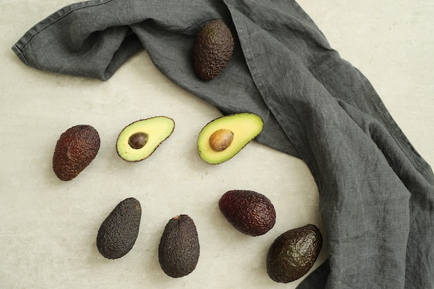 Whole and cut avocados on gray cloth