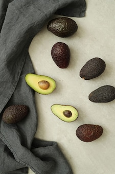 Whole and cut avocados on grey cloth