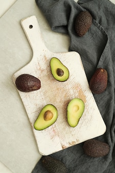 Whole and cut avocados on wooden cutting board