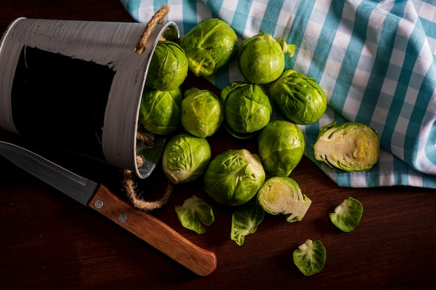 Whole and cut brussels sprouts falling from a small bucket