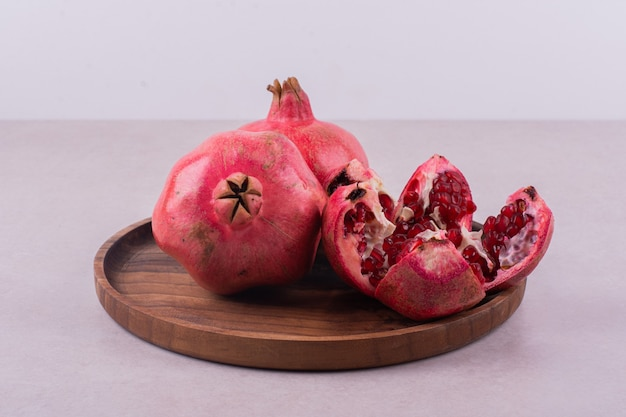 Whole and cut pomegranates on wooden plate.