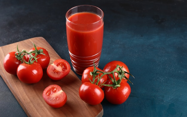 Whole and cut tomatoes and a glass of tomato juice on the blue background.