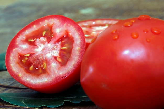 Whole and cut tomatoes on wooden background