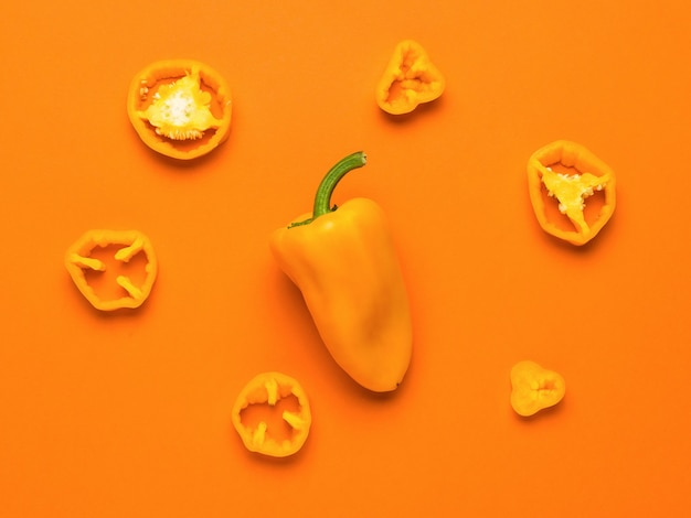 Whole and cut yellow bell pepper on a green background. vegetarian food.