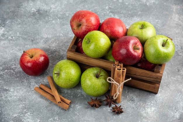 Целые вкусные зеленые и красные яблоки в деревянной коробке.