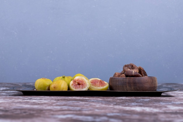 Whole, dry and sliced figs in a metallic tray and in a wooden cup on blue.