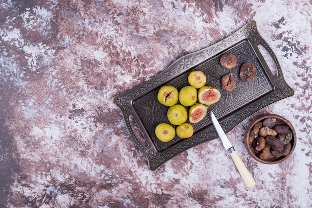Whole, dry and sliced figs in a metallic tray and in a wooden cup with a knife aside.