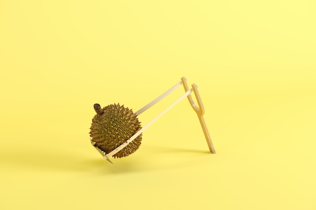 Whole durian in a slingshot on yellow background