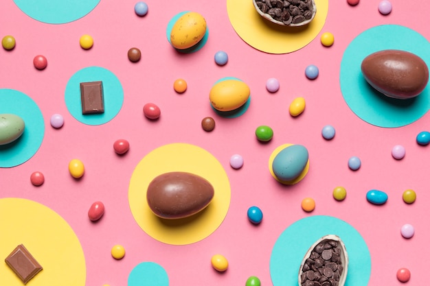 Whole easter eggs and colorful candies on pink background