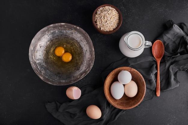 Uova intere e tuorli in piatti di legno e metallo.