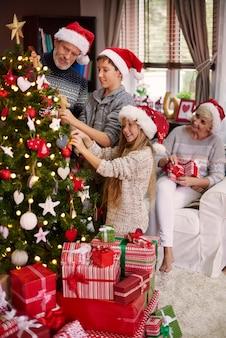 온 가족이 크리스마스 트리를 드레싱